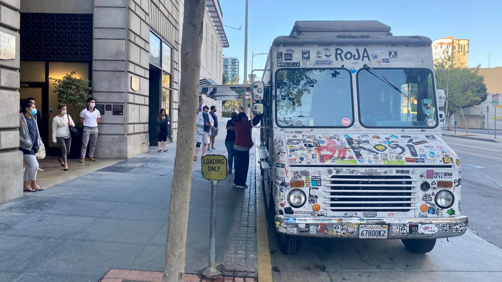 LOS ANGELES, CA, APR 2020: masked residents in Downtown wait for food at sticker-covered Kogi catering truck, parking outside apartments during Covid-19 virus lock down.