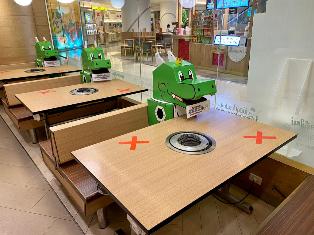 Bangkok, Thailand-May 20,2020: A restaurant in Thailand use its mascot green dragon to accompany guests who come to dine in isolated tables amid COVID-19 pandemic crisis.
